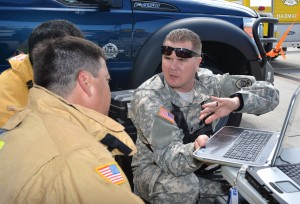 National Guard Nuclear Medical Science Officer First Lt. Keith Hapenney, 9th Civil Support Team (CST), works together with firefighters of the Honolulu Fire Department to analyze potential chemical hazard readings during exercise Kai Malu O'Hawaii 2015 at the Honolulu International Airport May 7. Exercise Kai Malu O' Hawaii, meaning into protected waters of Hawaii, is an annual exercise sponsored by the Hawaii National Guard's 93rd Civil Support Team (CST) designed to test first responders at the local, state and federal levels.