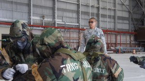 Staff Sgt. Frederick Villoso, chemical biological and nuclear environment survival instructor with the 154th Civil Engineering Squadron observes Hawaii Air National Guard Airmen as they don their chemical protective suites to MOPP 4, looking for errors and providing helpful hints, Aug. 9, 2015, Joint Base Pearl Harbor-Hickam. (U.S. Air National Guard Photo by Tech. Sgt. Andrew Jackson)